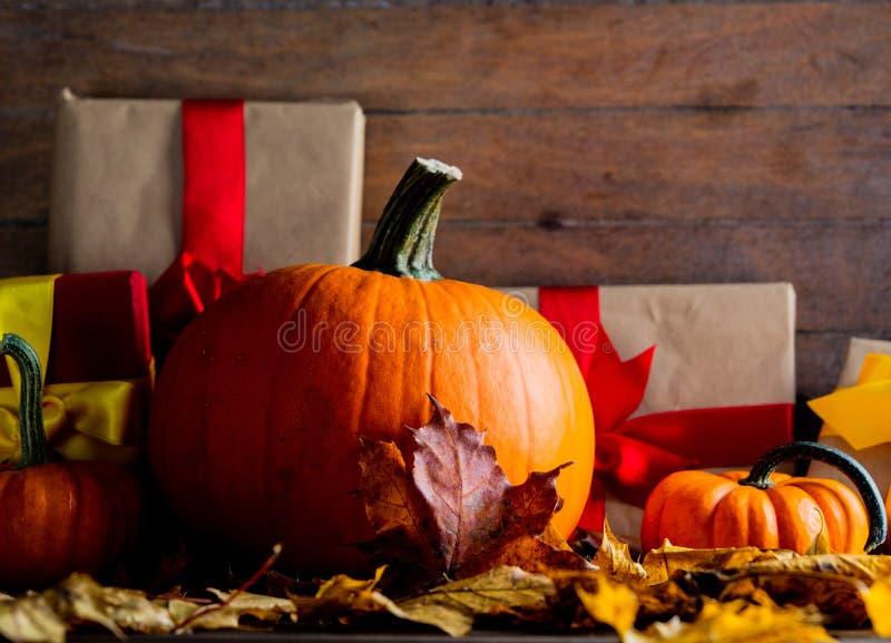 Подарочные коробки с смычком и кленовыми листами и тыквами стоковое изображение rf