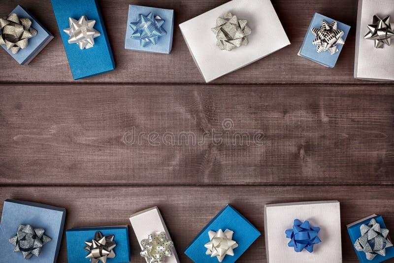 Подарочные коробки украшенные со смычками лежат на краях темной деревянной предпосылки presents В разбивочном космосе экземпляра стоковые изображения