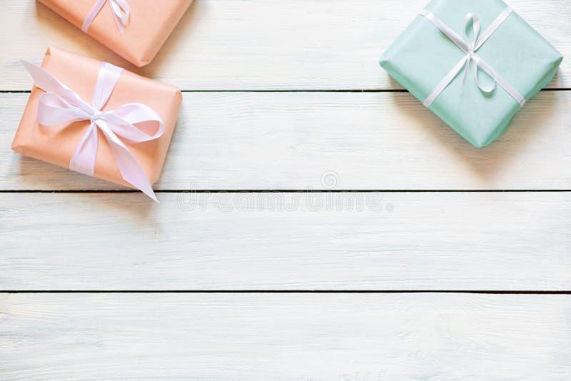 Подарочные коробки цветов персика и мяты на белой деревянной предпосылке r Свободное место для вашего положения текста плоского стоковые изображения rf