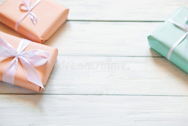 Подарочные коробки цветов персика и мяты на белой деревянной предпосылке r Свободное место для вашего положения текста плоского стоковое изображение