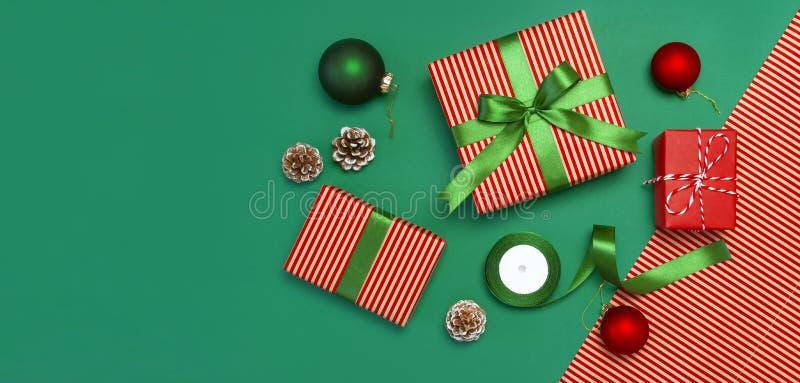 Подарочные коробки, шарики рождества, игрушки, конусы ели, лента на зеленой предпосылке Праздничный, поздравление, подарки на рож стоковое фото