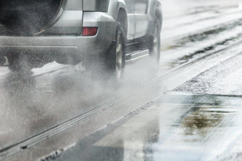 Подача выплеска дождевой воды от колес серебряного автомобиля кроссовера двигая быстро в город дневного света с выборочным фокусо стоковое фото rf