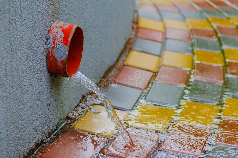 Подачи воды вниз с тротуара вдоль водосточной трубы во время весеннего дождя стоковые фотографии rf