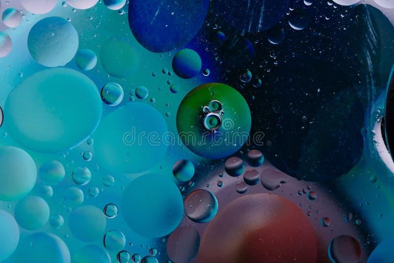 Подачи предпосылки макроса пузыря масла воды зеленый цвет абстрактной жидкостный голубой розовый стоковое фото rf