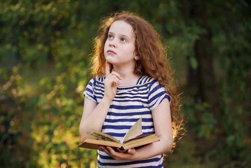 Подбородок задумчивой маленькой девочки касающий с думая стороной выражения стоковые фото