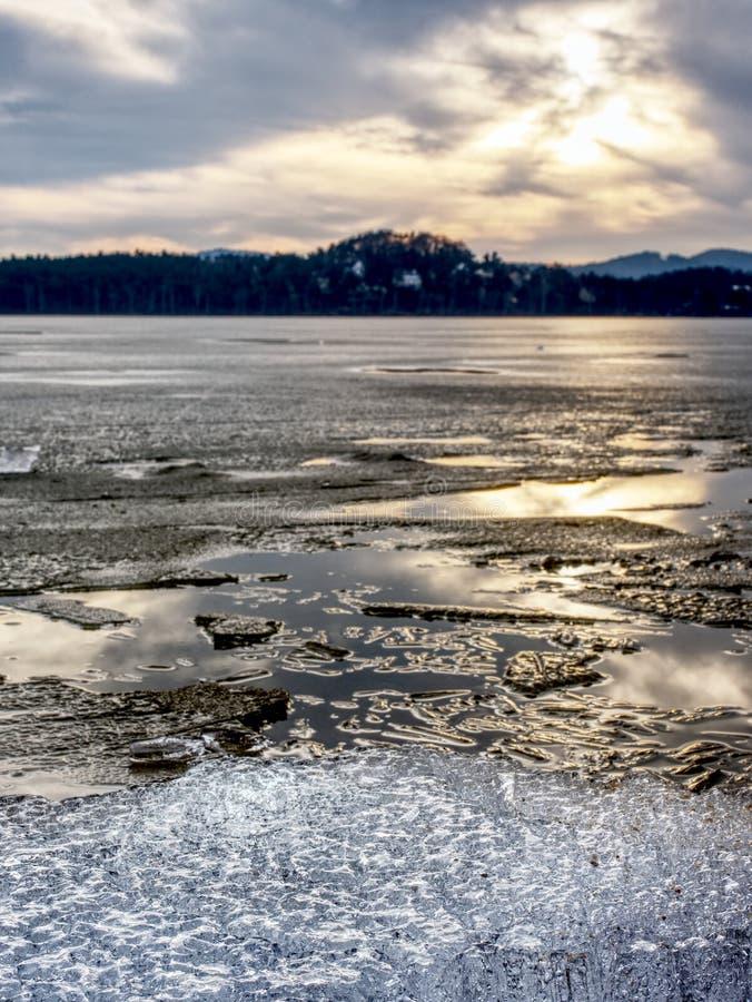 Подвергли действию берег под плавя льдом Закройте вверх по взгляду для того чтобы граничить между льдом и темной водой стоковое фото