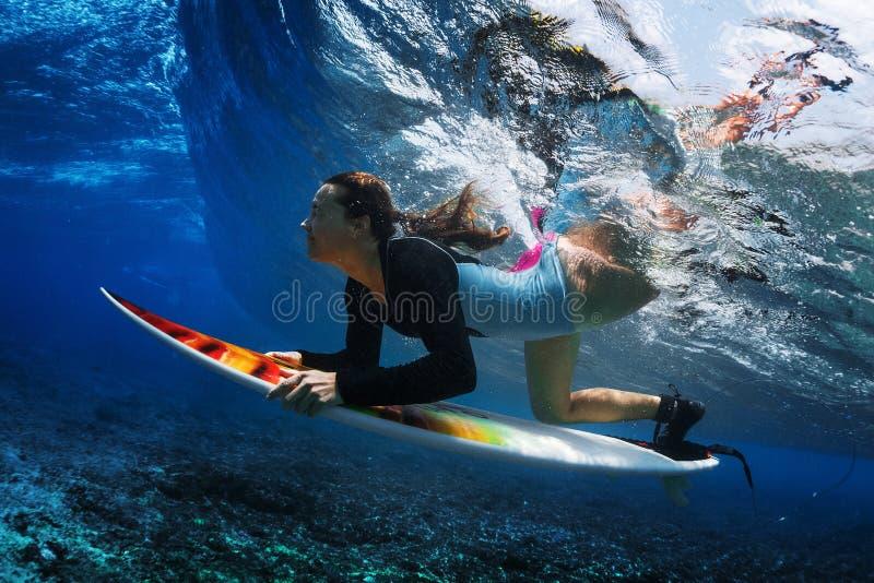 Подводная съемка серфера молодой женщины стоковое изображение