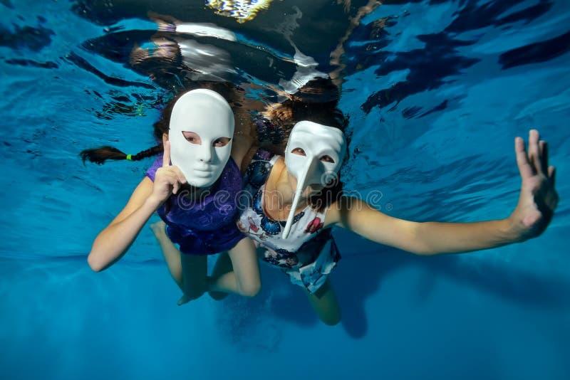 Подводный театр 2 необыкновенных девушки плавают и играют под водой в бассейне на голубой предпосылке в белых масках masquerade стоковые изображения rf