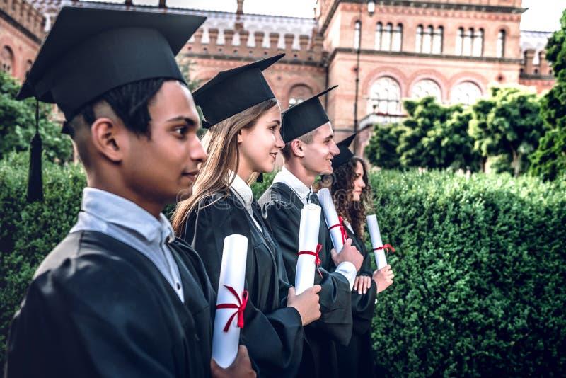 Подготавливайте для новых начал! Счастливые студент-выпускники стоят в ряд в университете outdoors в хламидах с дипломами в руке стоковое изображение