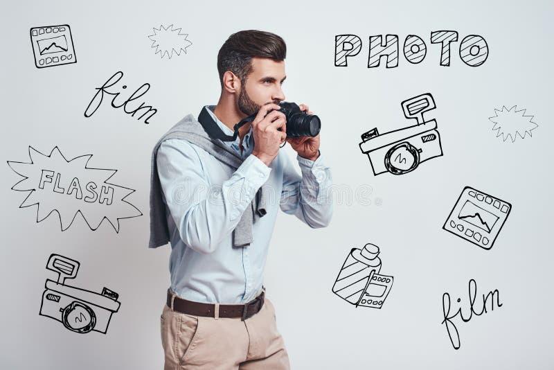Подготавливайте для того чтобы сделать фото Молодой привлекательный человек идет сделать цифровую фотокамеру photoon пока стоящ п стоковые изображения rf