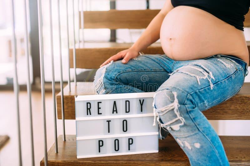Подготавливайте для того чтобы хлопнуть концепция - портрет беременной женщины с концом вверх живота на лестницах в доме стоковая фотография rf
