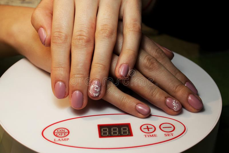 подготавливайте шеллак маникюра маникюр выполненный студентом ложь рук на специальной лампе ультрафиолетова Розовая штейновая отд стоковые фотографии rf