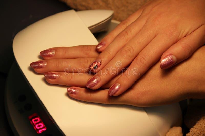 подготавливайте шеллак маникюра покрасьте золото шеллака розовое стоковые фото