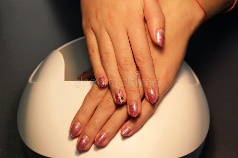 подготавливайте шеллак маникюра покрасьте золото шеллака розовое стоковые изображения rf