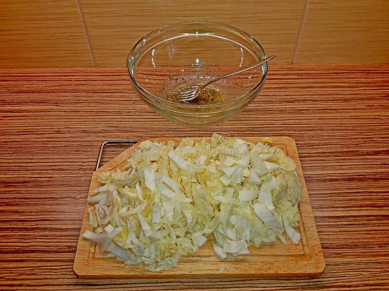 Подготавливающ отрезанный салат капусты на деревянной разделочной доске перед устанавливать его в стеклянном шаре с маслом, специ стоковое фото