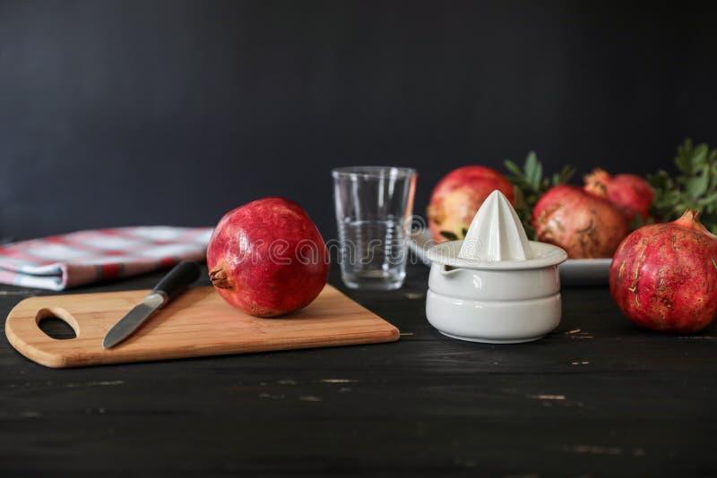 Подготавливающ сделать свежий сок гранатового дерева, ingtredients, kitchenware на черной деревянной предпосылке стоковое изображение rf