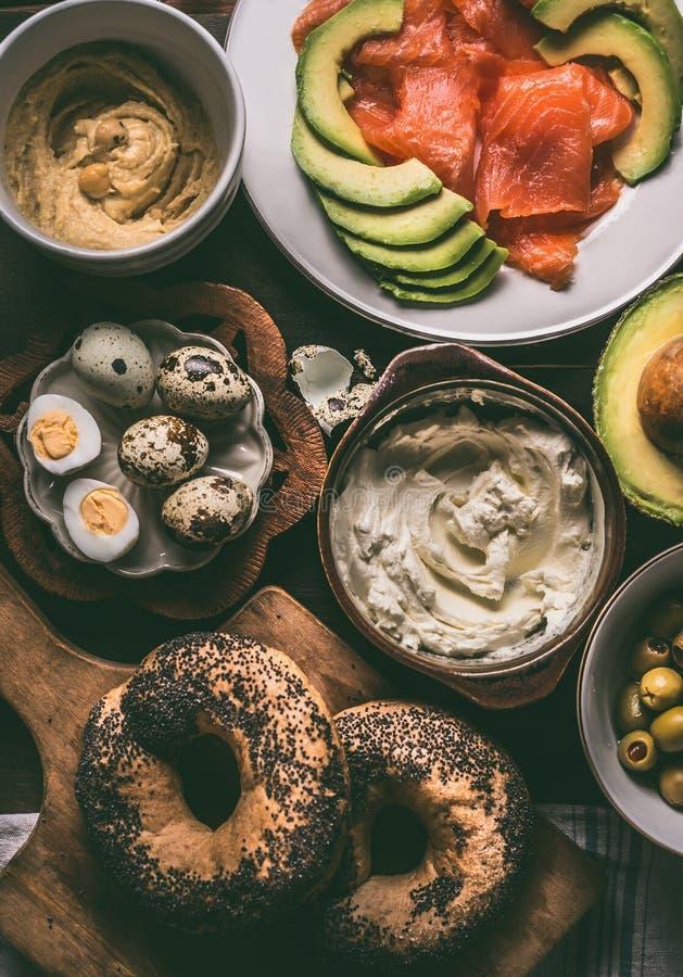 Подготовка завтрака с хлебом бейгл, семгами, авокадоом, свежим сыром, hummus и сваренными яйцами триперсток на темное деревенское стоковая фотография