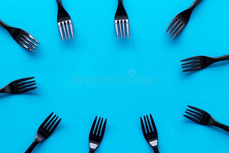 Подготовка концепции еды для меню ресторана с пластиковой рамкой вилок на голубом взгляде сверху предпосылки стоковая фотография
