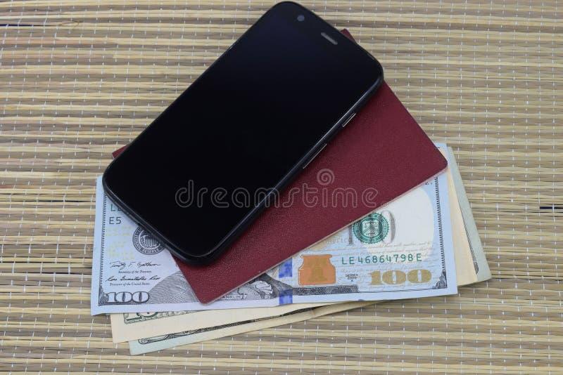 Подготовка на каникулы, пасспорт с деньгами для остатков на таблице и сотовый телефон в пути стоковые изображения