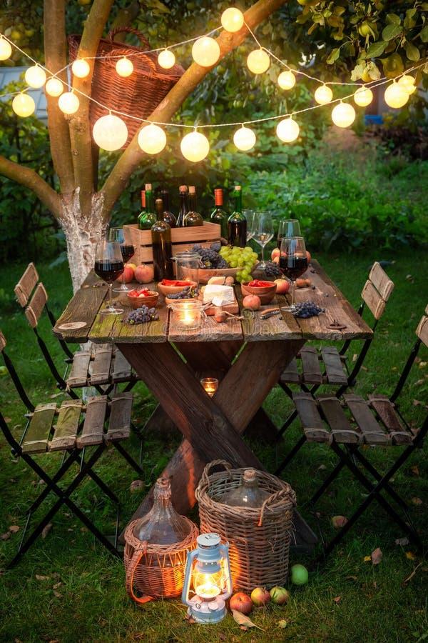 Подготовка на ужин с вином в саде лета стоковая фотография rf