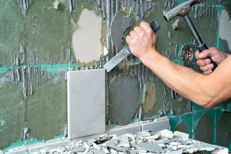 Подготовка ремонта ванная комната Человек извлекая старые плитки стоковые изображения rf