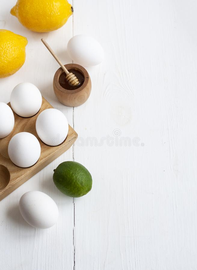 Подготовка соуса: мед, яйца, лимон и лайм Продукты лежат на белом деревянном фоне стоковое фото