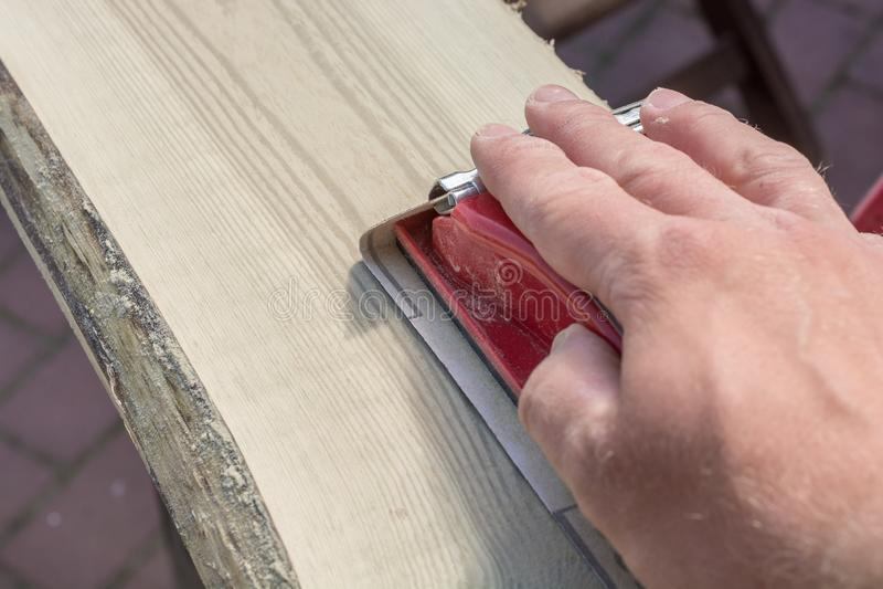 Подготовка старой деревянной доски путем молоть с блоком руки зашкурить стоковое фото