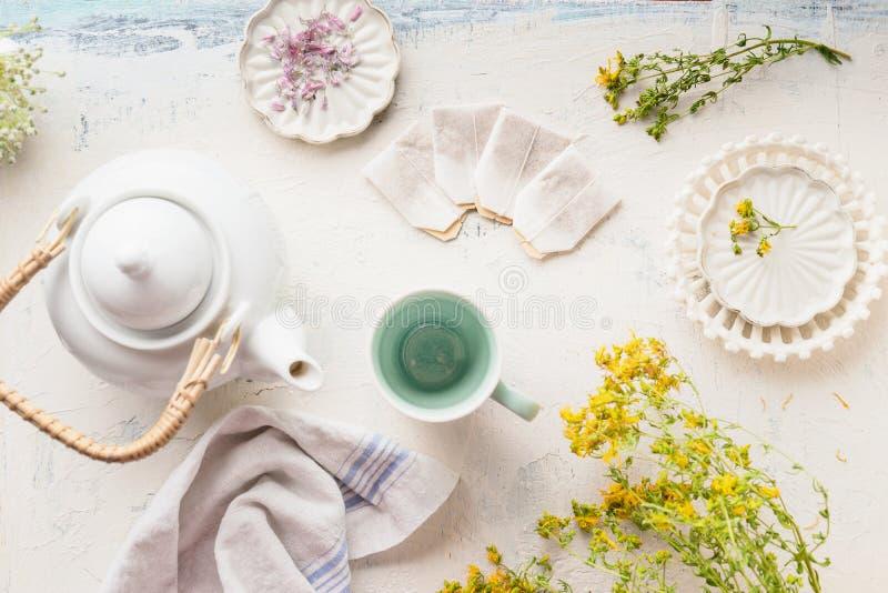 Подготовка травяного чая с дикими лекарственными растениями tutsan, взгляд сверху Белая установка чая со свежими травами и пакети стоковая фотография