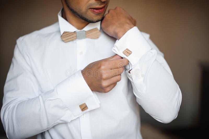 Подготовка утра Groom Молодой бородатый получать groom одел в рубашке свадьбы с деревянной бабочкой стоковое фото rf