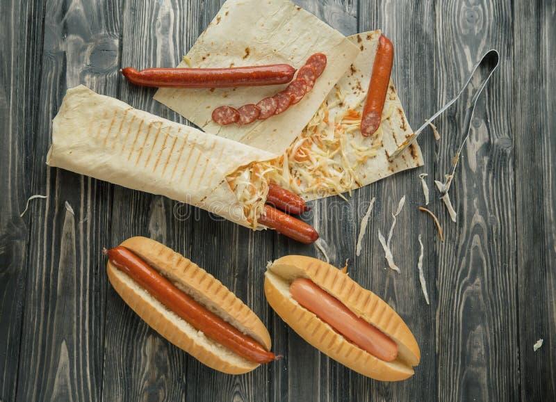 Подготовка хот-догов с сосиской и сосисками стоковое изображение rf