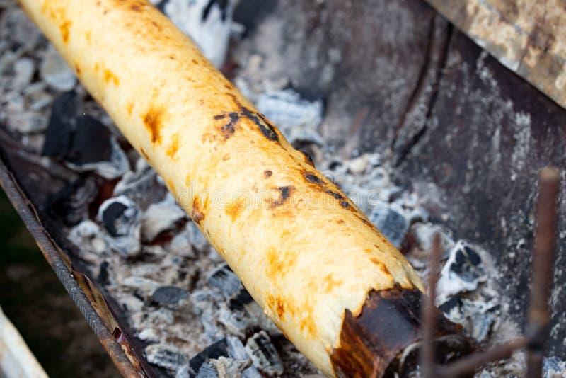 Подготовка CHOCHOCA - пища для батата на острове Чилоэ, Чили Хлеб чиилотанского картофеля, приготовленный на деревянной палке стоковое фото rf