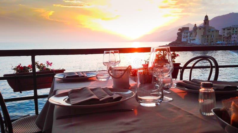 Подготовленная таблица с впечатляющим заходом солнца на побережье Генуи стоковые фото
