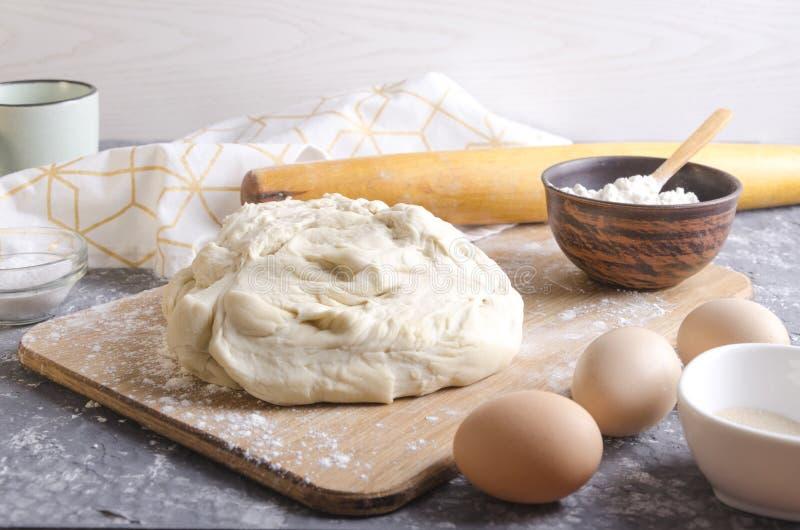 Подготовленное тесто пиццы на деревянной доске Ингредиенты для praparation большего домодельного теста Чашка молока, яя, муки, вр стоковые фотографии rf