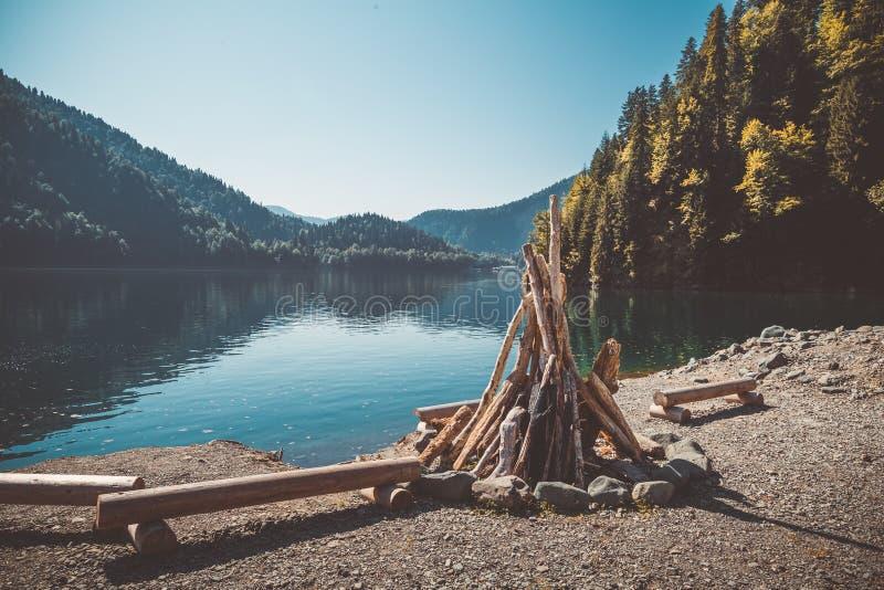 Подготовленный для разжигать большой костер и стенды от журналов на береге красивого озера при чистая вода окруженная к mo стоковые фотографии rf