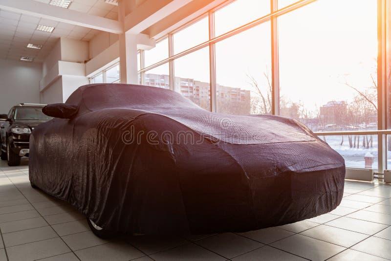 Подготовленный подарок на автосалоне, автомобиль спорт закрыл с голубым случаем сделанным особенной ткани, зашитый в индивидуальн стоковая фотография rf