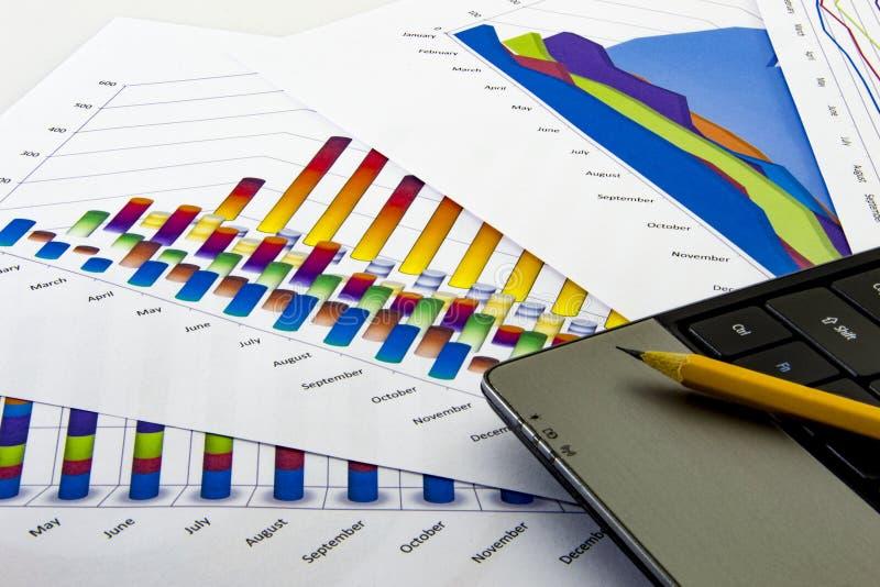 Подготовлять рапорт Голубые диаграммы и диаграммы Бизнес-отчеты и куча документов на серой предпосылке отражения стоковое изображение rf