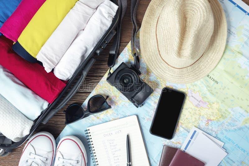 Подготовьте аксессуары и детали перемещения, для нового путешествия, пакуя одежды в сумке чемодана на деревянной доске, плоское п стоковые изображения rf