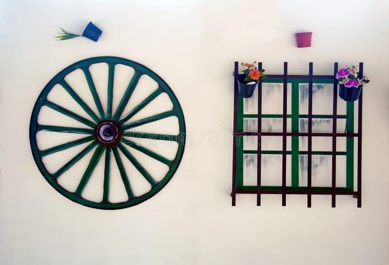 Поддельное колесо телеги и окно на белой стене стоковые фотографии rf
