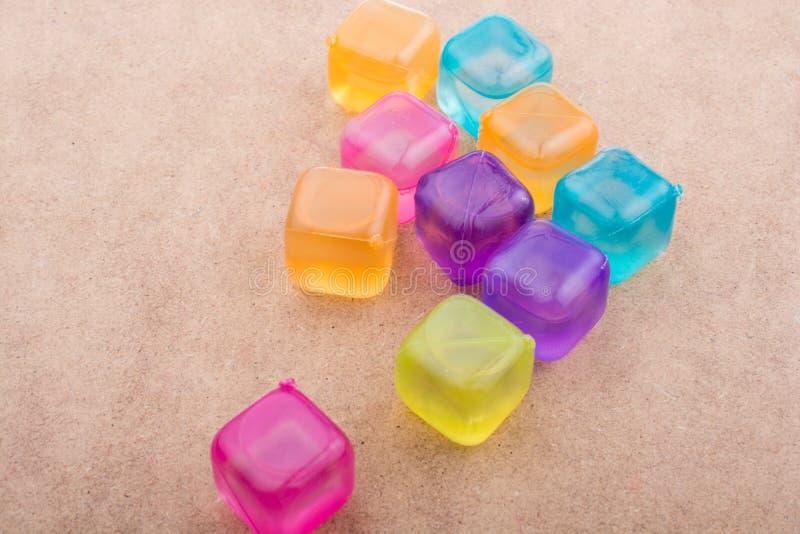 Поддельные красочные кубы льда на древесине стоковое фото