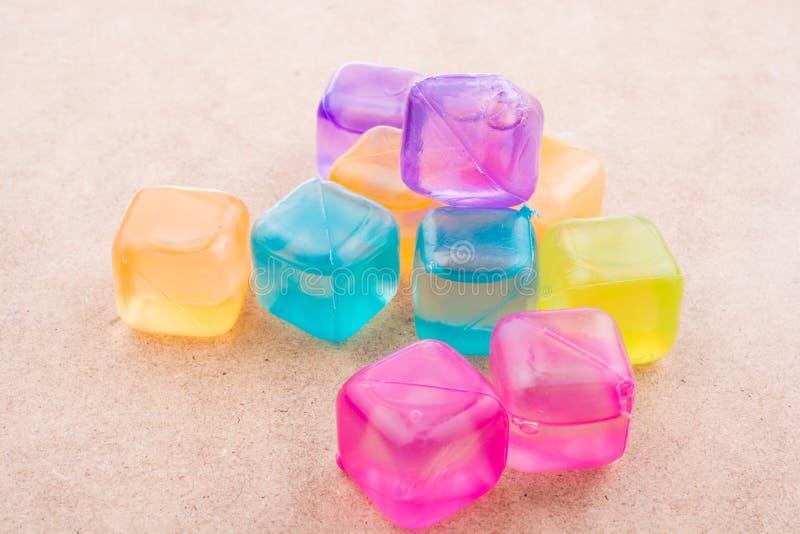 Поддельные красочные кубы льда на древесине стоковое изображение