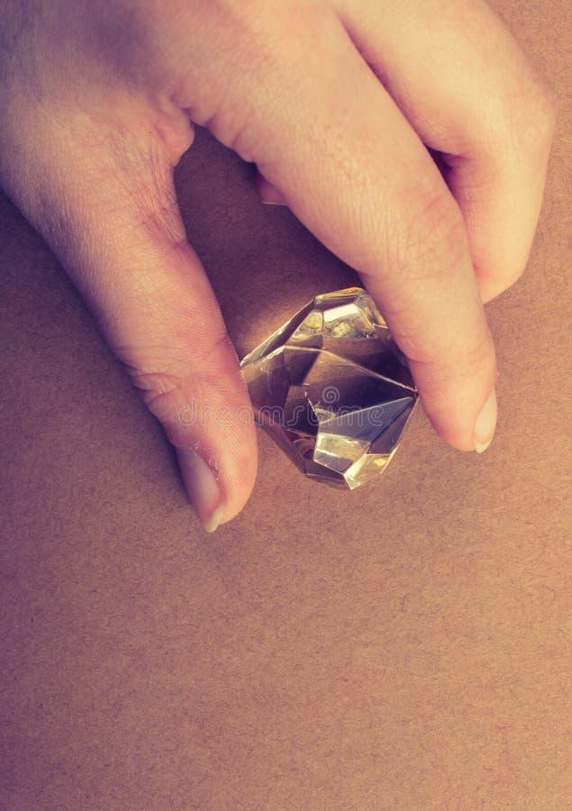 Поддельный камень диаманта в руке стоковая фотография