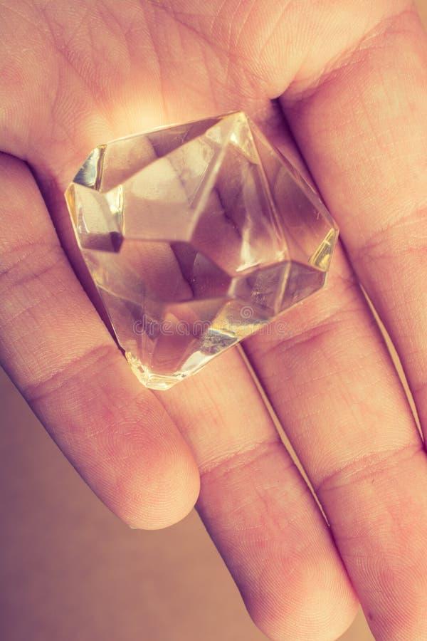 Поддельный камень диаманта в руке стоковые фото