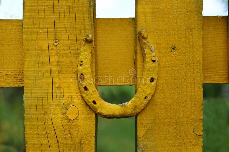 Подкова на загородке покрашена с желтой краской стоковое фото