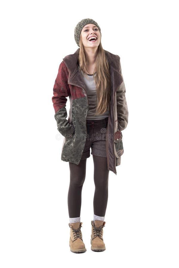 Подлинная беспристрастная молодая стильная женщина в теплой одежде смеясь крепко стоковые фото