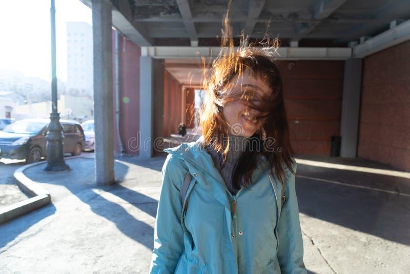 Подлинный городской портрет маленькой девочки в голубом windbreaker Ветер раздражает красные волосы и волосы покрывают его сторон стоковое фото rf