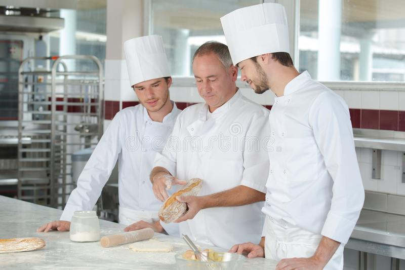 Подмастерья в хлебопекарне уча от опытного профессионала стоковые изображения rf