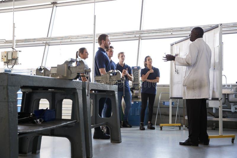 Подмастерья инженерства стоят на представлении тренировки, низком угле стоковое фото