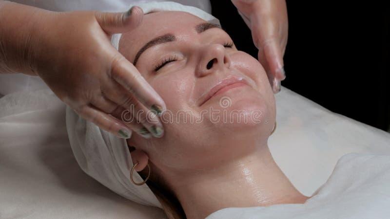 Подмолаживание кожи в центре косметологии Девушка с закрытыми глазами усмехается на процедуре в салоне красоты Руки cosmeto стоковая фотография