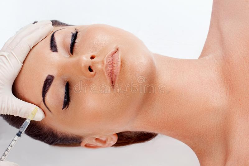 Подниматься стороны Портрет стороны красивой женщины с идеальной ровной кожей получая Hyaluronic впрыску коллагена стоковое изображение