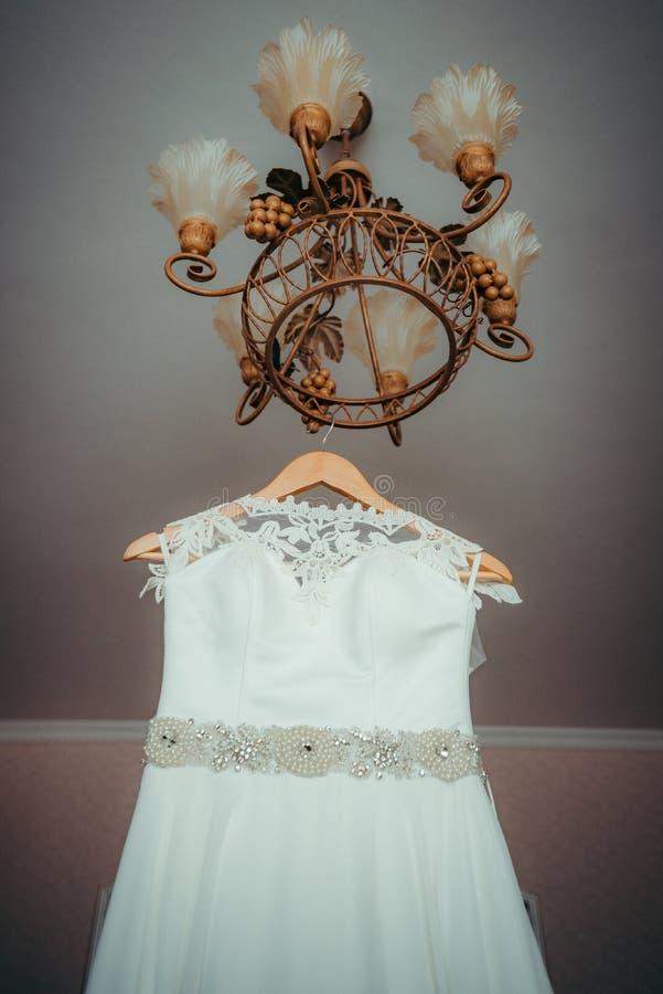Поднимающий вверх взгляд на красивом платье свадьбы при украшения вручая на люстре Вертикальная съемка стоковые фотографии rf